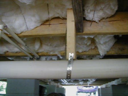 "The parish requires R-13 underneath the floor. Notice the steel wire ""Tiger Teeth"" that easily hold the insulation in place. You should not have a vapor barrier here because moisture might accumulate above it. So just tear off the vapor barrier so it can breathe."