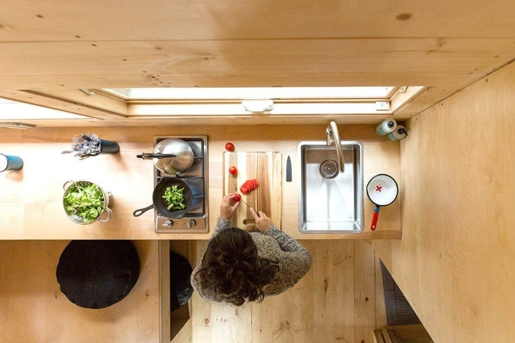 Getaway tiny kitchen with woman cutting vegetables
