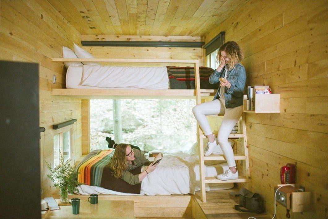 Two women in bunk beds in a Getaway cabin